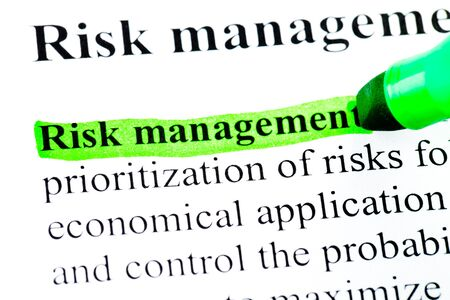 Risk management definition highlighted by green marker on white photo