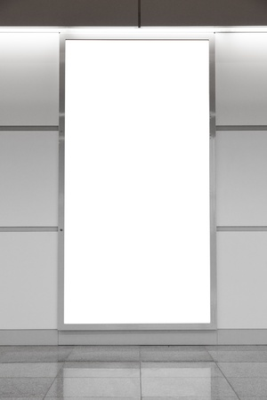 Vertical blank billboard on a bright wall photo