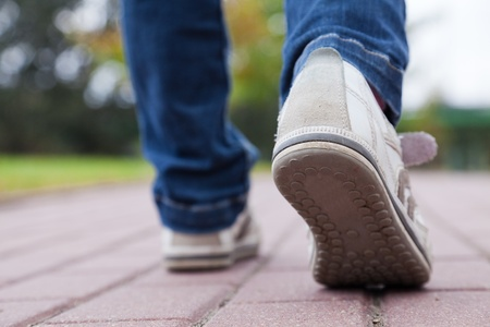 footpath: Teenager walking in sport shoes on pavement in autumn day Stock Photo