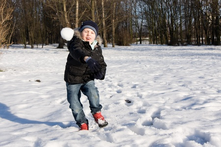 Boy throwing snowball in cold winter day photo