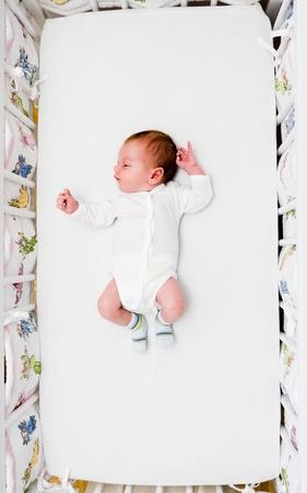 Newborn small boy sleeping in his big bed photo