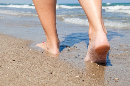 Woman walking barefoot on sunny beach in summer day photo
