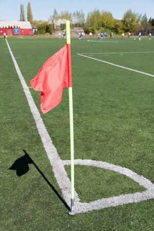 Red flag in corner of soccer field in summer day photo