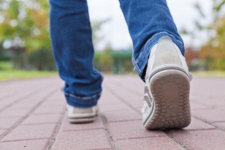 caminando: Adolescente caminando en los zapatos del deporte en el pavimento en el d�a de oto�o