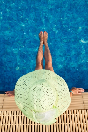 girl sit: Woman in green hat resting in resort pool Stock Photo