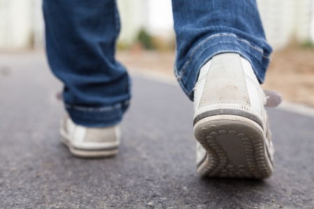 foot wear: Teenager walking in sport shoes on pavement in autumn day Stock Photo