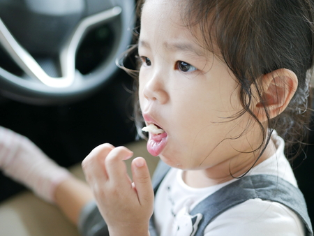 Little Asian baby girl, 24 months old, is choking while eating a piece of apple