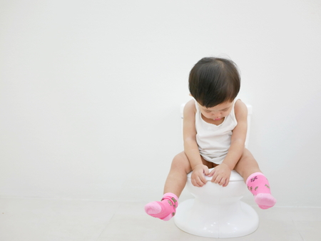 Een Aziatische baby van 11 maanden oud die op een babytoilet zit voor een zindelijkheidstraining