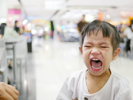 A sudden uncontrollable burst of crying of an Asian baby girl in a shopping mall - baby behavior Standard-Bild
