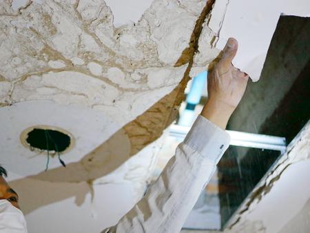 La mano de un hombre tirando / derribando el techo de un baño, ya que está siendo destruido por una infestación severa de termitas Foto de archivo