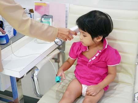 Asian baby girl having oxygen amount in her blood, heart rate, and temperature measured, using an oximeter and a portable digital thermometer by a pediatric nurse assistant Stok Fotoğraf