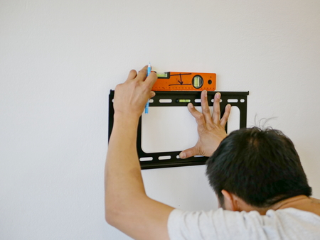 Asian technician hands holding a TV wall mount against the wall while looking for the right angle to make a mark for a drilling Stockfoto - 105086154