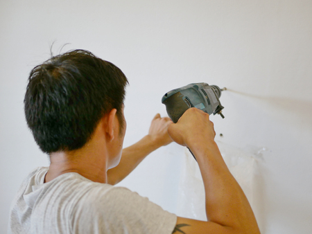 An electric drill being used by Asian handy man drilling into concrete wall Stock fotó
