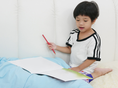 Asian baby girl, 30 months old, holding a pencil and about to writing and drawing on a book - pencil grasp development begins when children are babies Stock Photo