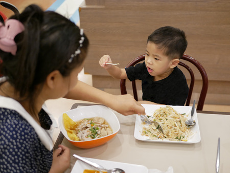 Little Asian baby, 30 months old, picking up a beansprout from her food (Padthai) and trying to negotiate with her mother that she does not want to eat it - baby refuses to eat vegetables Stock Photo