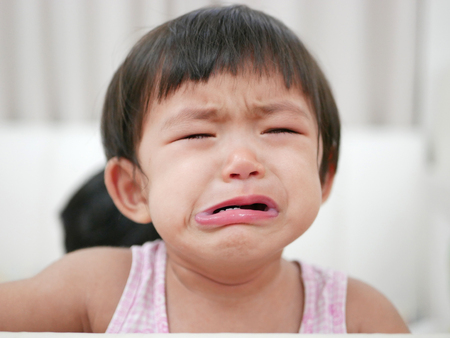 Crying Asian baby girl, 15 months old, with tears Standard-Bild - 105013634