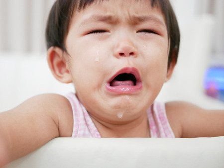 Crying Asian baby girl, 15 months old, with tears