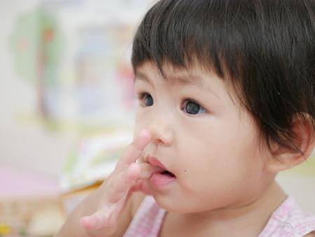 Klein Aziatisch babymeisje, 15 maanden oud, steekt haar vinger in haar mond - een van de meest voorkomende gedragingen / gewoonten in de vroege kinderjaren