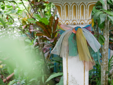 Old, pale, and grungy colorful fabric stripes wrapped around a spirit house in Thailand paying respect to the spirit living in the house