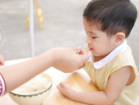 Asian mother's hand introducing a small peice of crispy deep-fried rice noodle to her little daughter for the first time - baby's development through encouraging them to try new foods / things