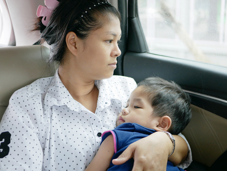 Asian mother carrying her baby while sitting in a moving car without a baby car seat - risk of taking a serious injury or death of a baby when car accident happens