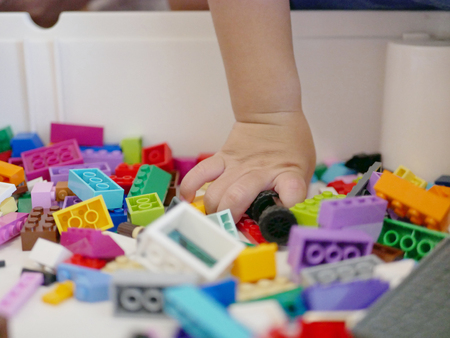 Little babys hand picking  choosing a piece of colorful interlocking plastic bricks