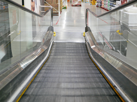 Close up of a moving shopping trolley escalators steps that is about to collapse on each other, creating a flat platform to make it easier to get on and off the escalator