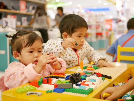 Little Asian baby girl (left) concentrates on pieces of colorful interlocking plastic bricks