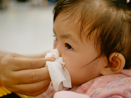 Close up of a mother hand squeezing her daughter running nose - cleanning a baby's stuffy nose