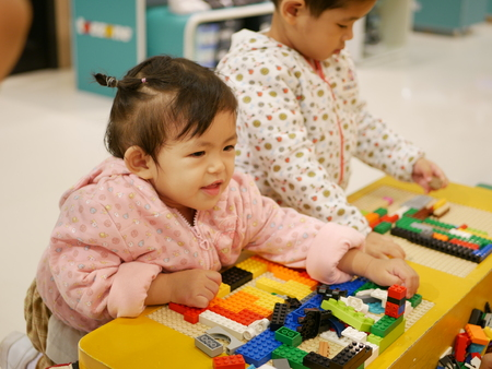 Little Asian baby girl (left) enjoys playing colorful interlocking plastic bricks  - child development through playing toys Banco de Imagens