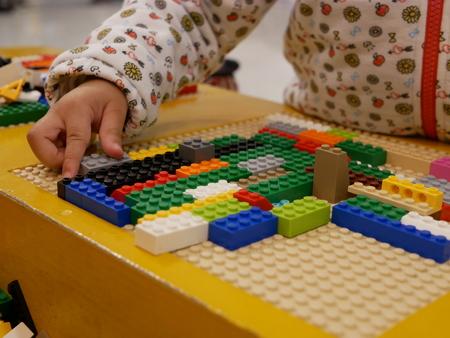 Hands of a baby playing colorful interlocking plastic bricks - child development through playing toys 版權商用圖片