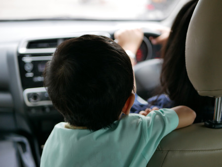 Asian baby standing on a driving car, does not want to sit and fasten the safety belt properly on the rear seat