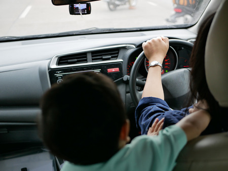 Asian baby playing and disturbing her mother on a driving car while she is trying to control a car Stock Photo