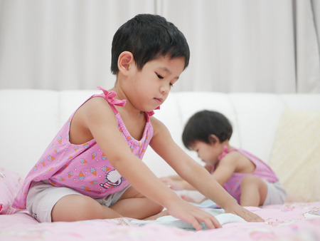Little Asian baby girl, 32 months old, (left) learning to fold clothes - baby's development through allowing them to help doing housework 版權商用圖片
