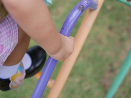 Close up of little baby's hand holding on a metalic stairs at a playground learning to climb it up - large muscle and motor development in baby through playing and exercising