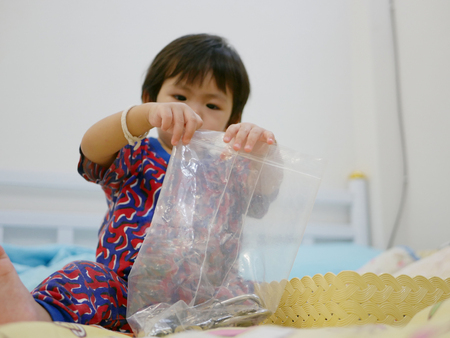 Little Asian baby girl, 17 months old, trying to close a plastic zip bag with keys inside