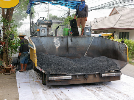 On-the-field laying asphalt concrete machine being used to make a road in a development project Imagens