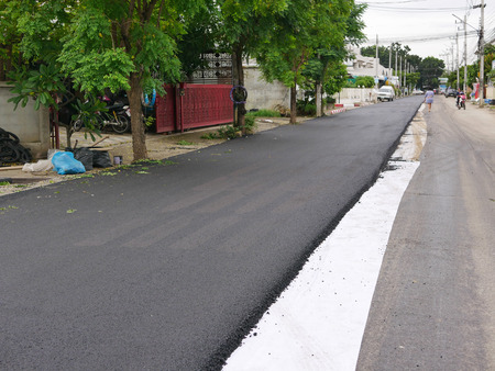 Fresh asphalt road in a development project has got already half of its surface repaired