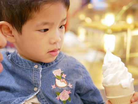 Little Asian baby being hungry for appealing ice cream cone in front of her