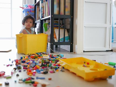 Messa a fuoco selettiva di una piccola bambina asiatica che cerca una scatola di blocchi ad incastro (giocattolo) e li sparge su tutto il pavimento