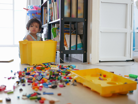 Selective focus of a little Asian baby girl searching a box of interlocking blocks (toy) and spreding them out all over the floor Stockfoto