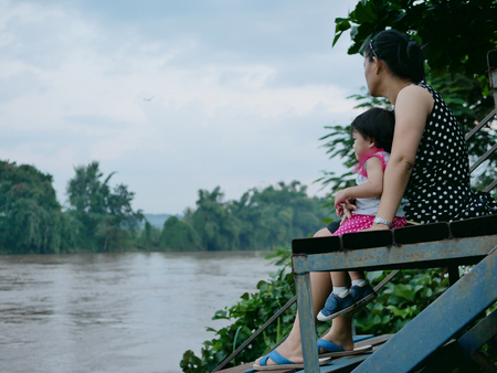 Asian mother and her little daughter by her side sitting on iron amphitheater experiencing the view of murky muddy river after rainfall, a natural phenomena
