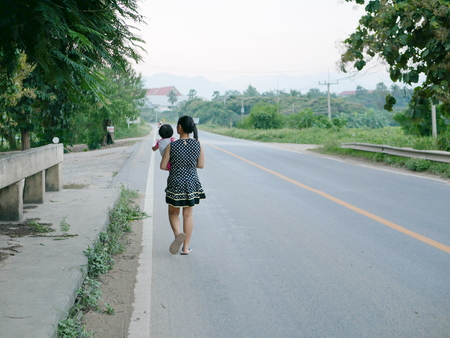 Young Asian mother carrying her little daughter and carelessly walk on the street