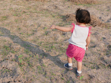 Little Asian baby girl, 18 months old, walking over uneven ground in an open field - toddler gross motor skill development