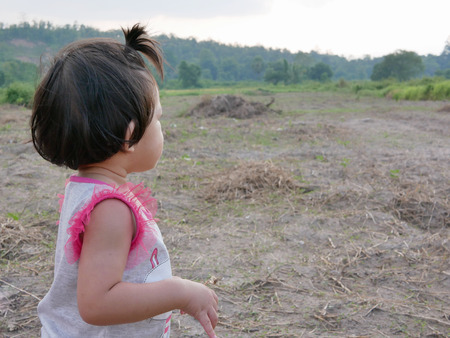 Little Asian baby girl, 18 months old, looking far away at an open field as she can see and interested in things in a further distance - toddler visual development