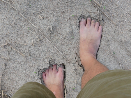 Bare feet of a man on natural soft sandy soil ground