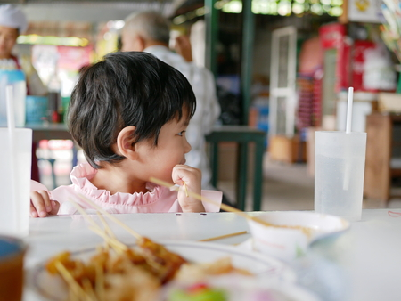 Little Asian baby girl, 34 months old, learning to eat pork satay on a stick by herself