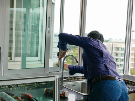 Asian technician installing a sliding window for high rise apartment building