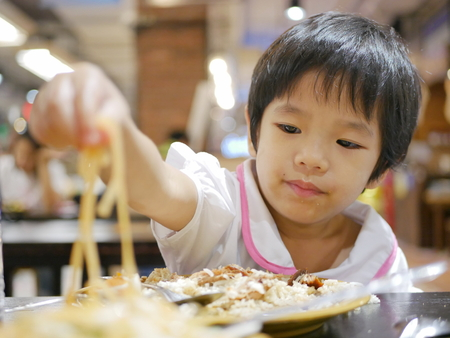 Little Asian babygirl, 34 months old, eating Pad Thai (Thai style stir fried noodles) with her hand 스톡 콘텐츠