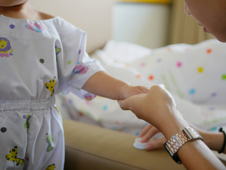 Pediatric nurse apply cream for local anaesthesia on a babys hand before performing IV insertion Stock Photo